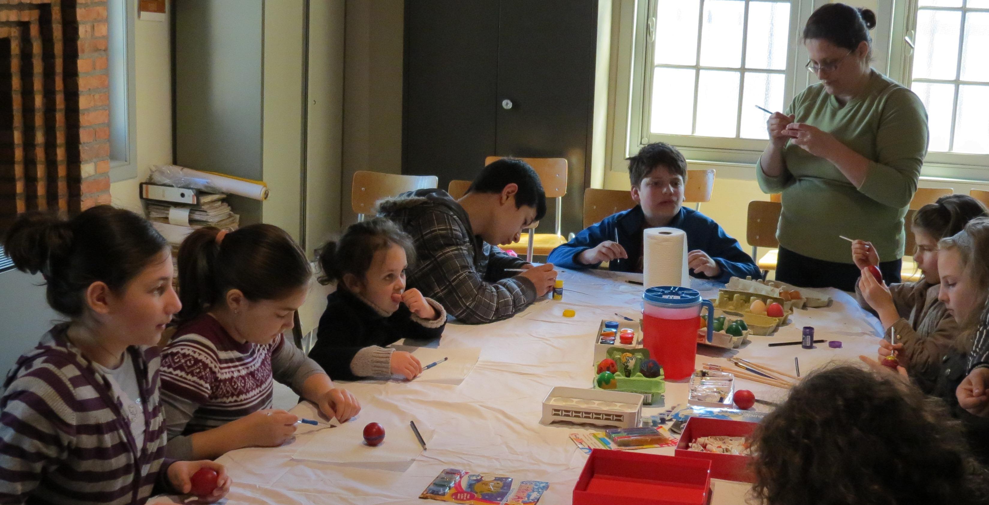 Copiii pictează ouă de Paști.